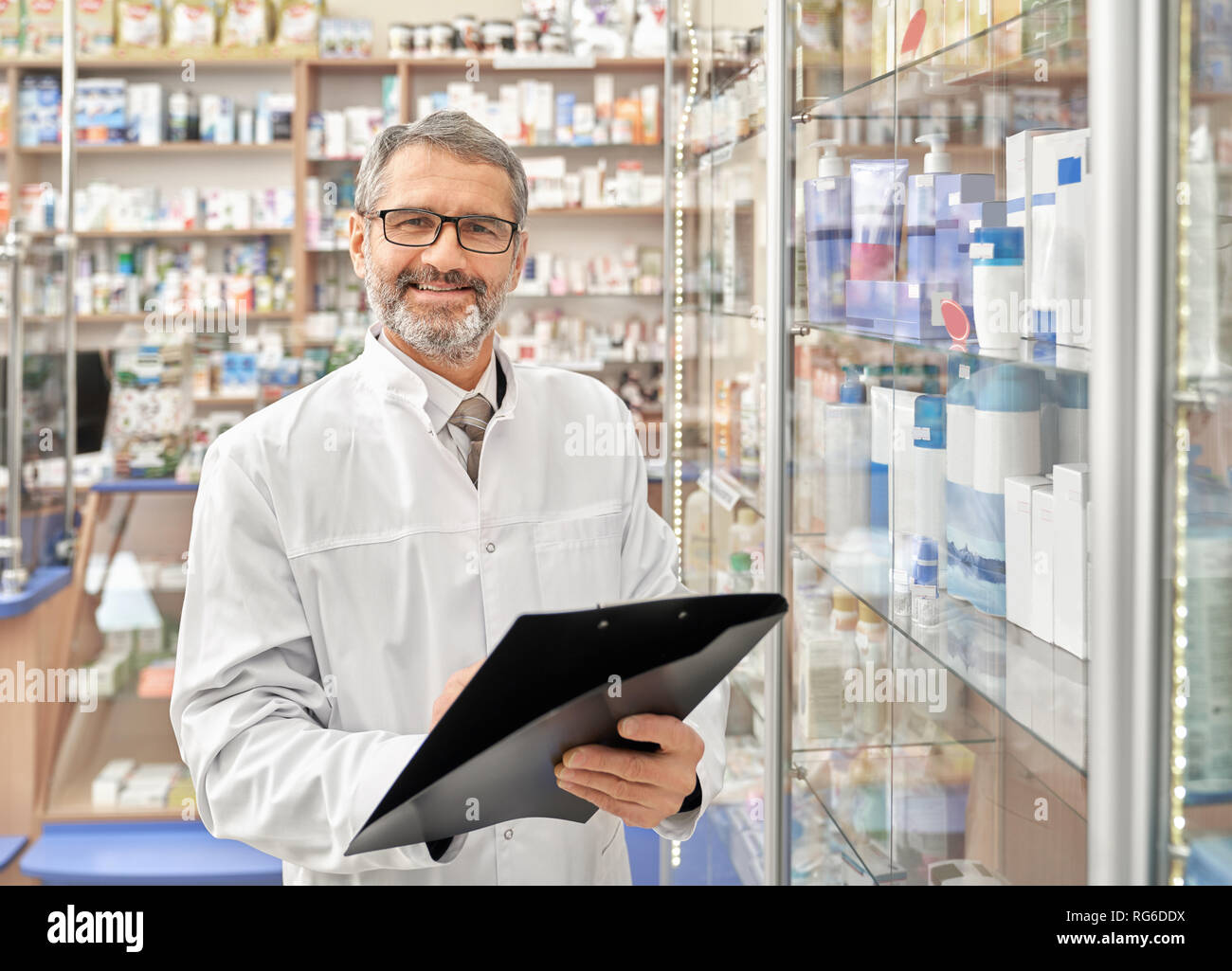 Cheerful mature man smiling, posing, standing near drugstore shelves with medicaments holding folder. Handsome bearded pharmacist with grey hair wearing in white lab coat and glasses. - Stock Image