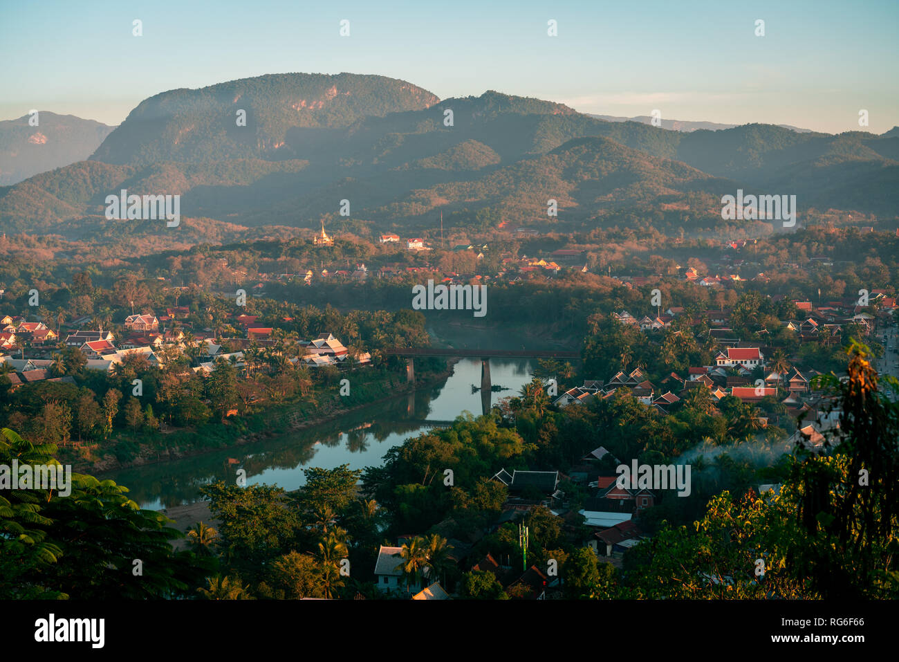 Sunset in Lunag Prabang, Laos. Beautiful clouds over the city. Mekong river between trees and houses. Winter in Laos - Stock Image