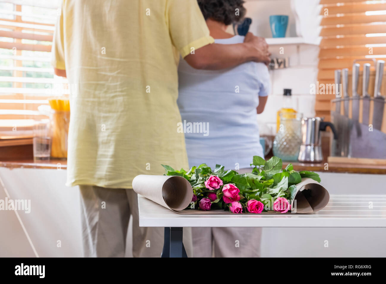 Close up pink rose with Asian Senior husband embrace wife while flower arrangement on table at kitchen at home in Valentine's Day.lovely senior couple Stock Photo