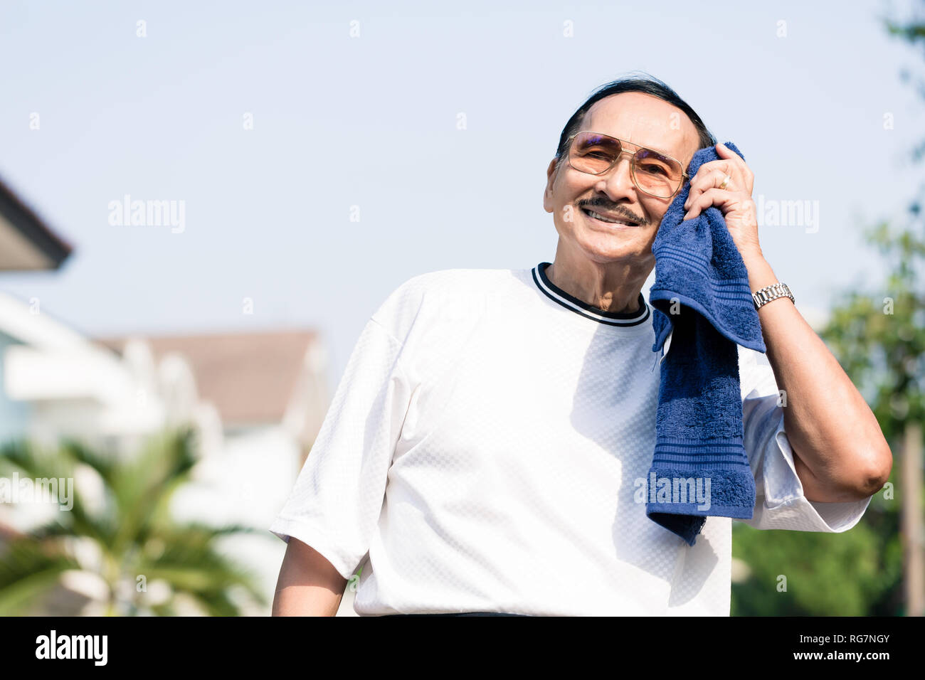 An elderly man wiping his sweat with napkin - Stock Image