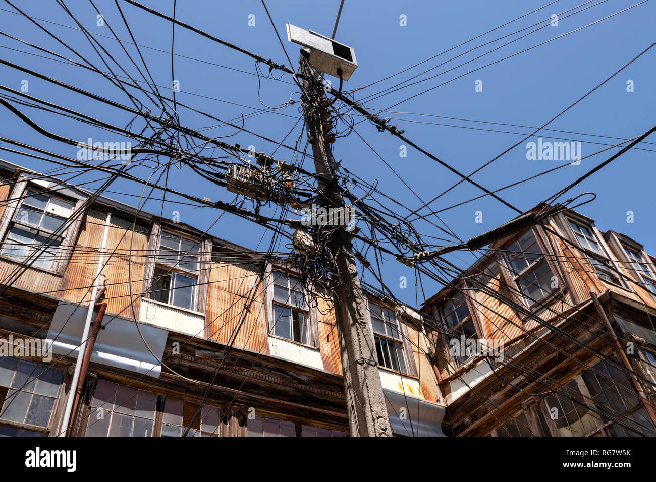 A seemingly tangled and disorganised collection of overhead cables in a street in Valparaiso, Chile. - Stock Image
