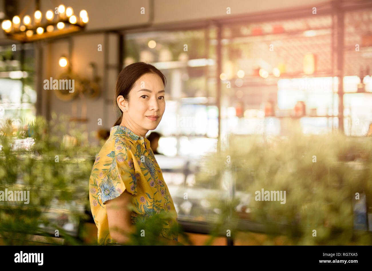 Beautiful middle aged Asian woman looking at camera in coffee shop. - Stock Image