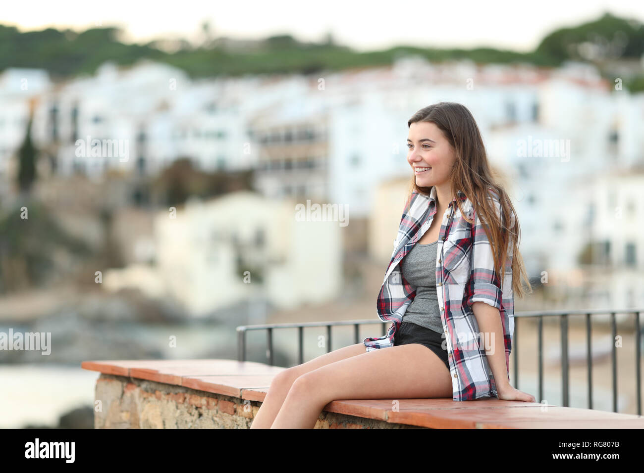 Happy teenager relaxing contemplating landscape sitting on a ledge in a town outskirts - Stock Image