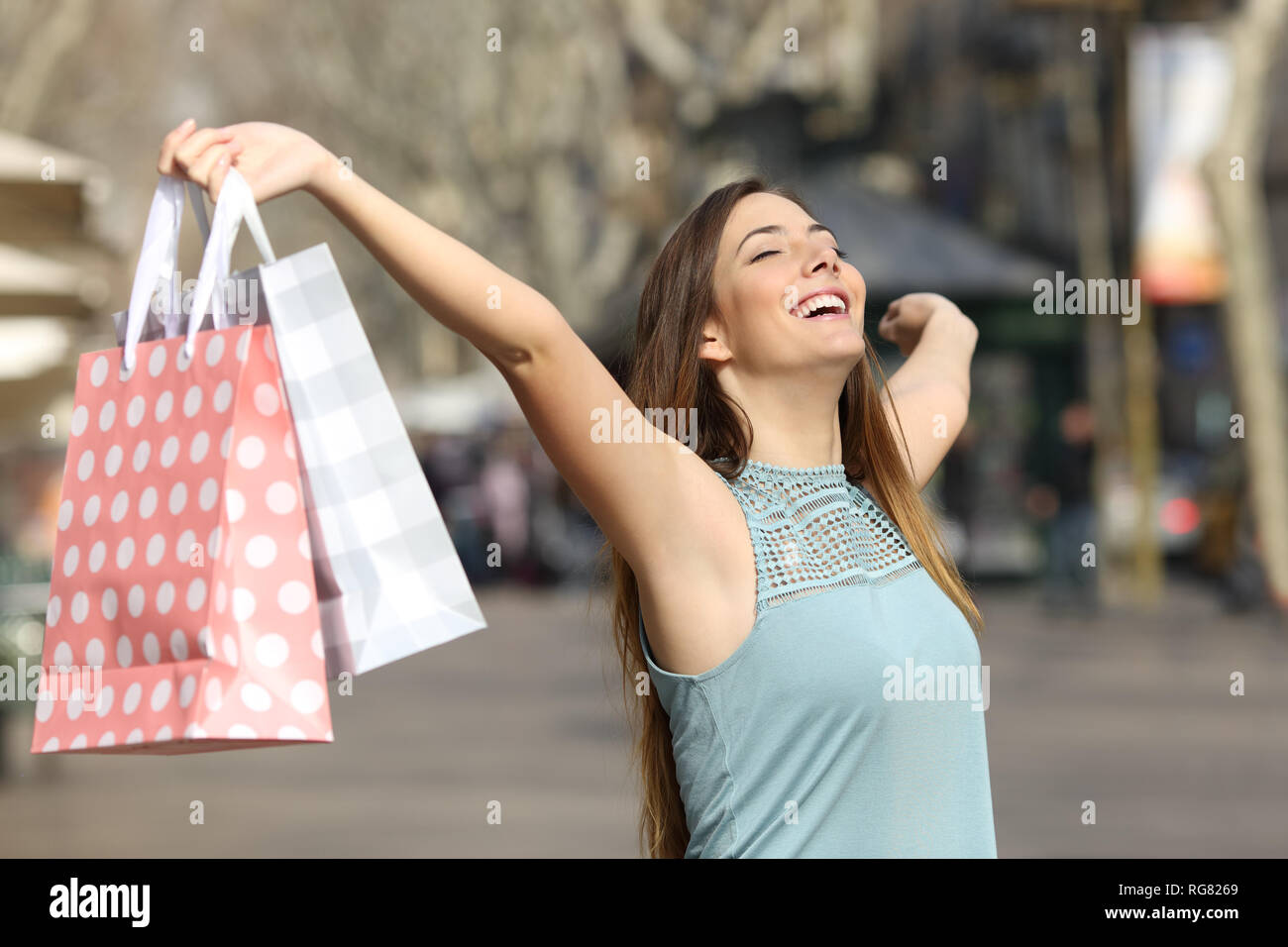 Happy shopper holding shopping bags raising arms in a street - Stock Image