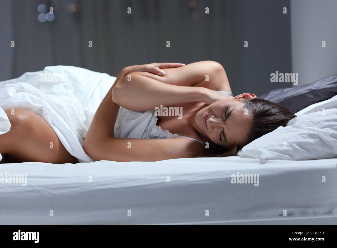 Woman complaining suffering neck ache sleeping with a bad pillow on a bed at home - Stock Image