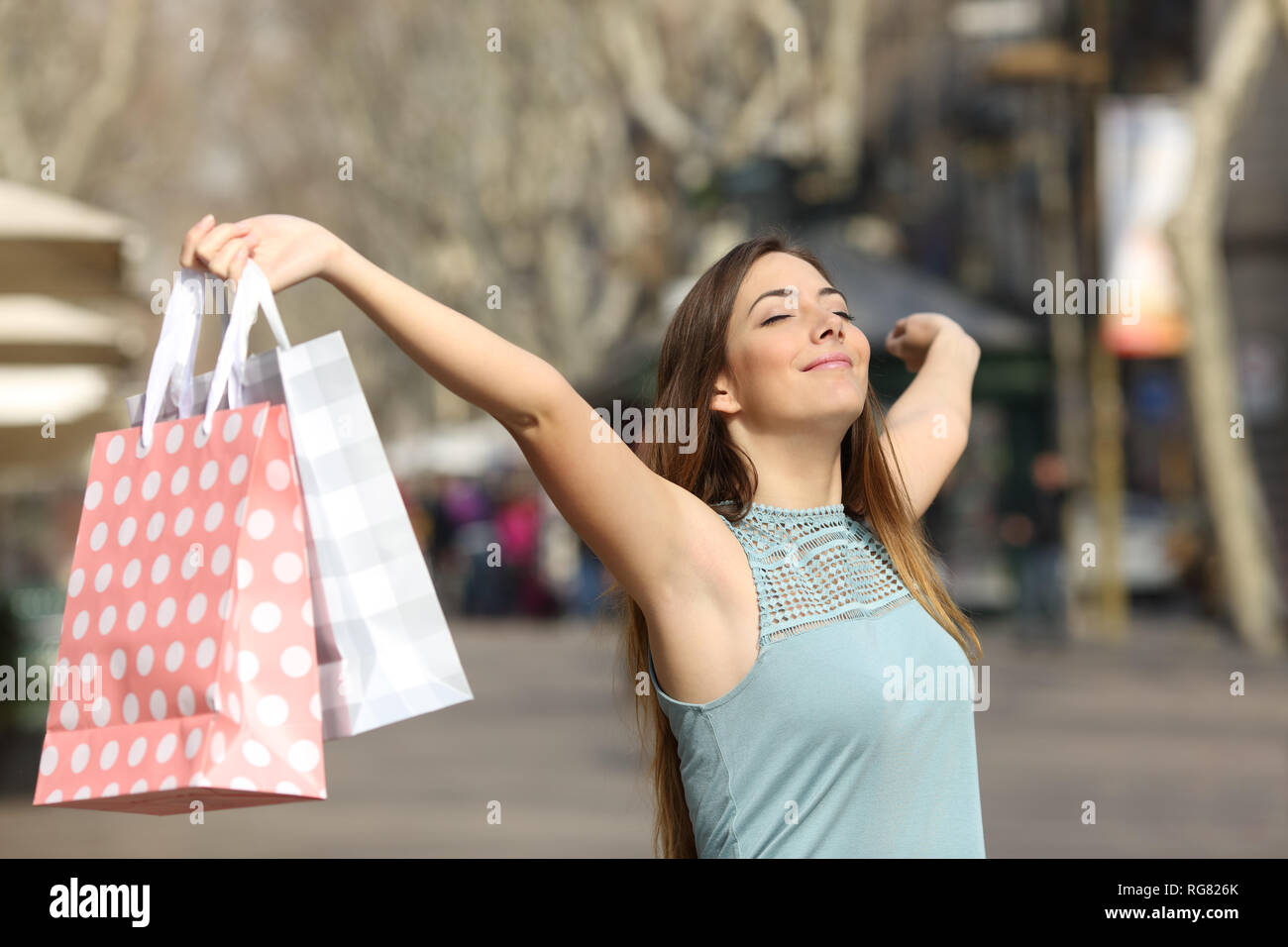 Shopper holding shopping bags raising arms in a city street - Stock Image