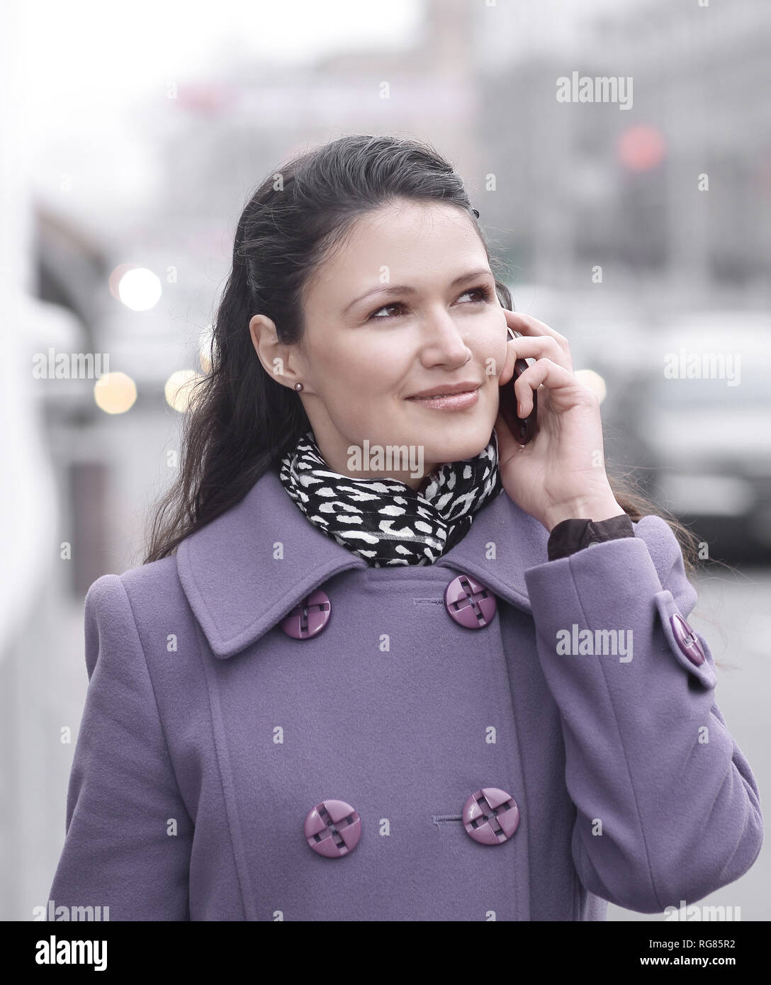 young woman listens to an interlocutor on a mobile phone - Stock Image