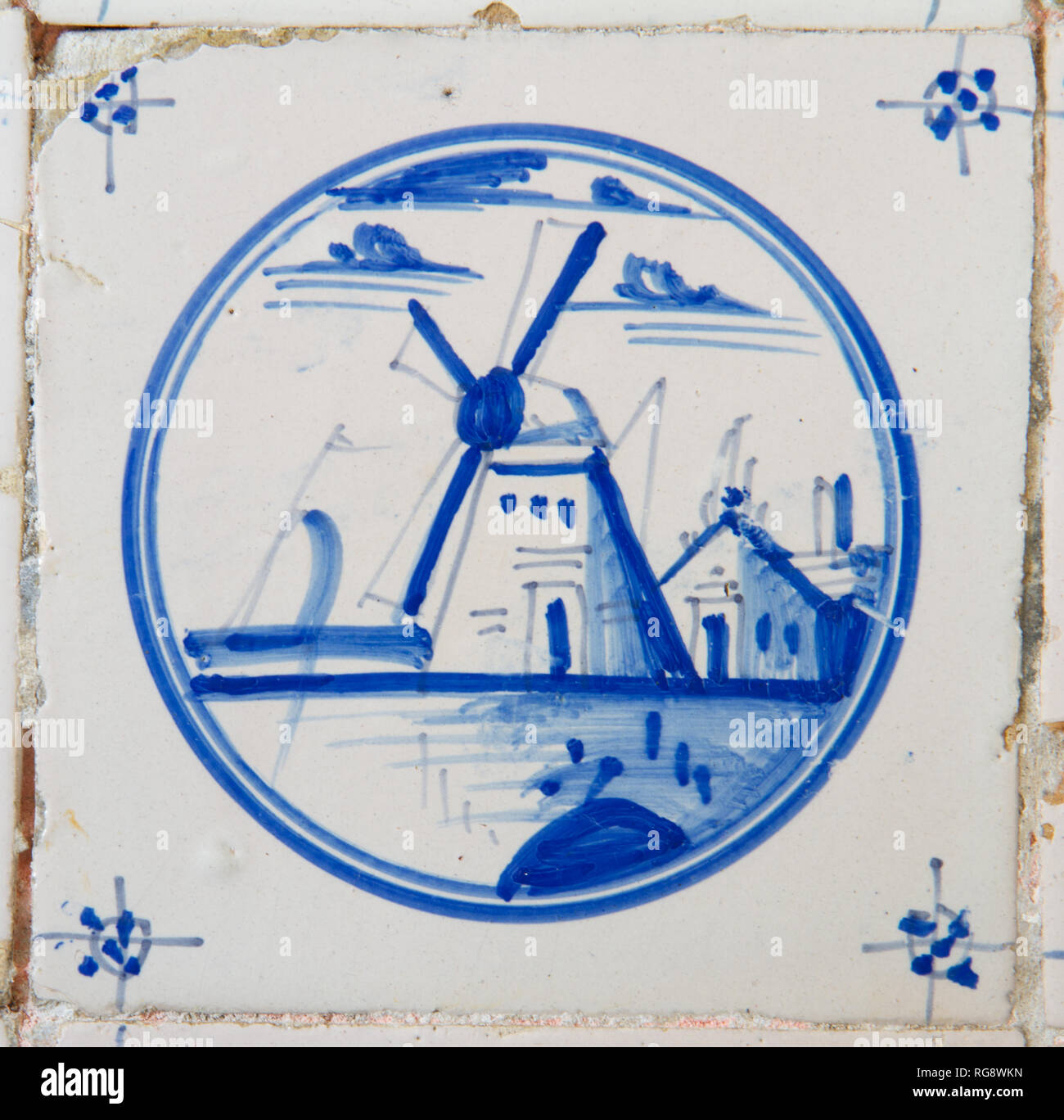 Delft blue and white tile with the painting of a windmill - Stock Image