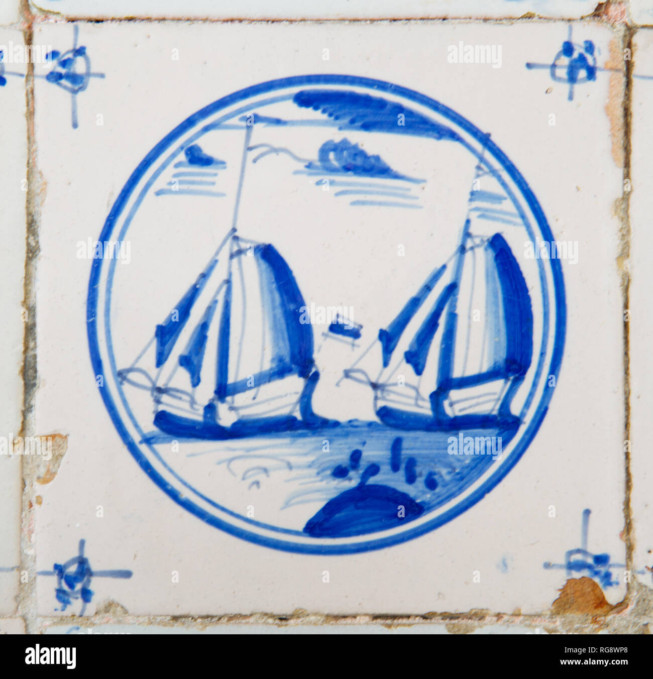 Delft blue and white tile with the painting of sailing ships - Stock Image