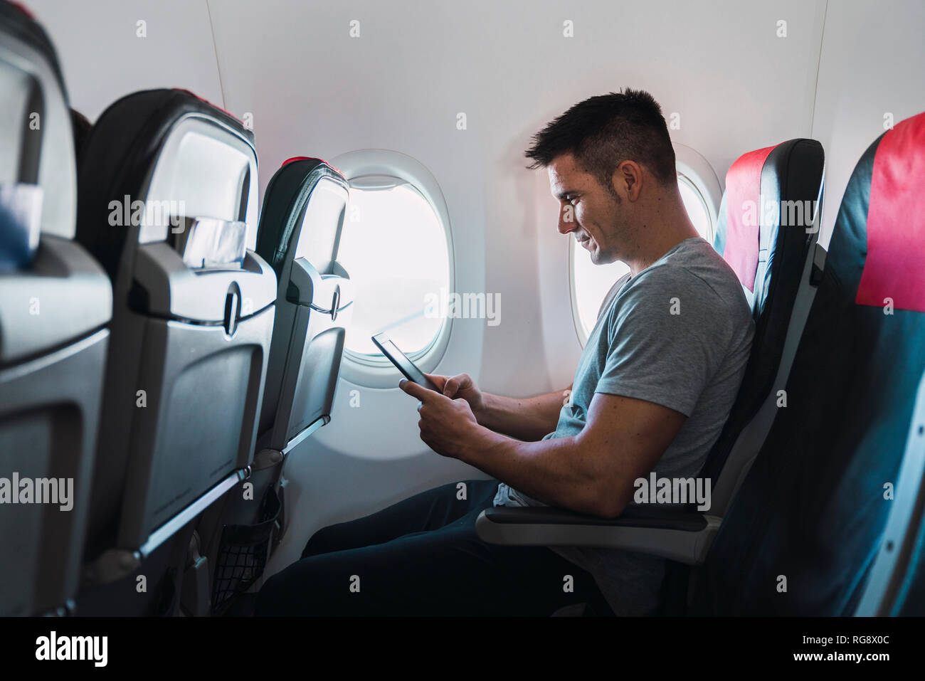 Man using ebook in airplane - Stock Image