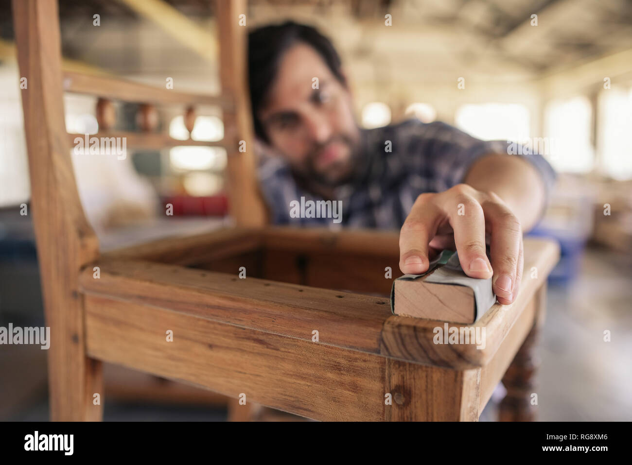 Skilled woodworker sanding a chair in his workshop - Stock Image