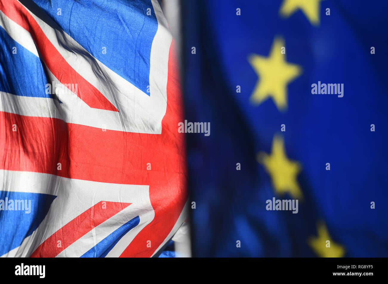 Union and European Union flags are flown outside the Houses of Parliament, London. - Stock Image