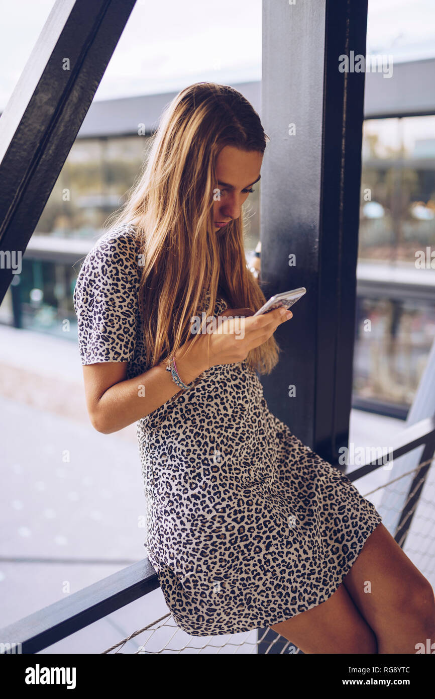 Attractive young woman in leopard print dress checking cell phone Stock Photo
