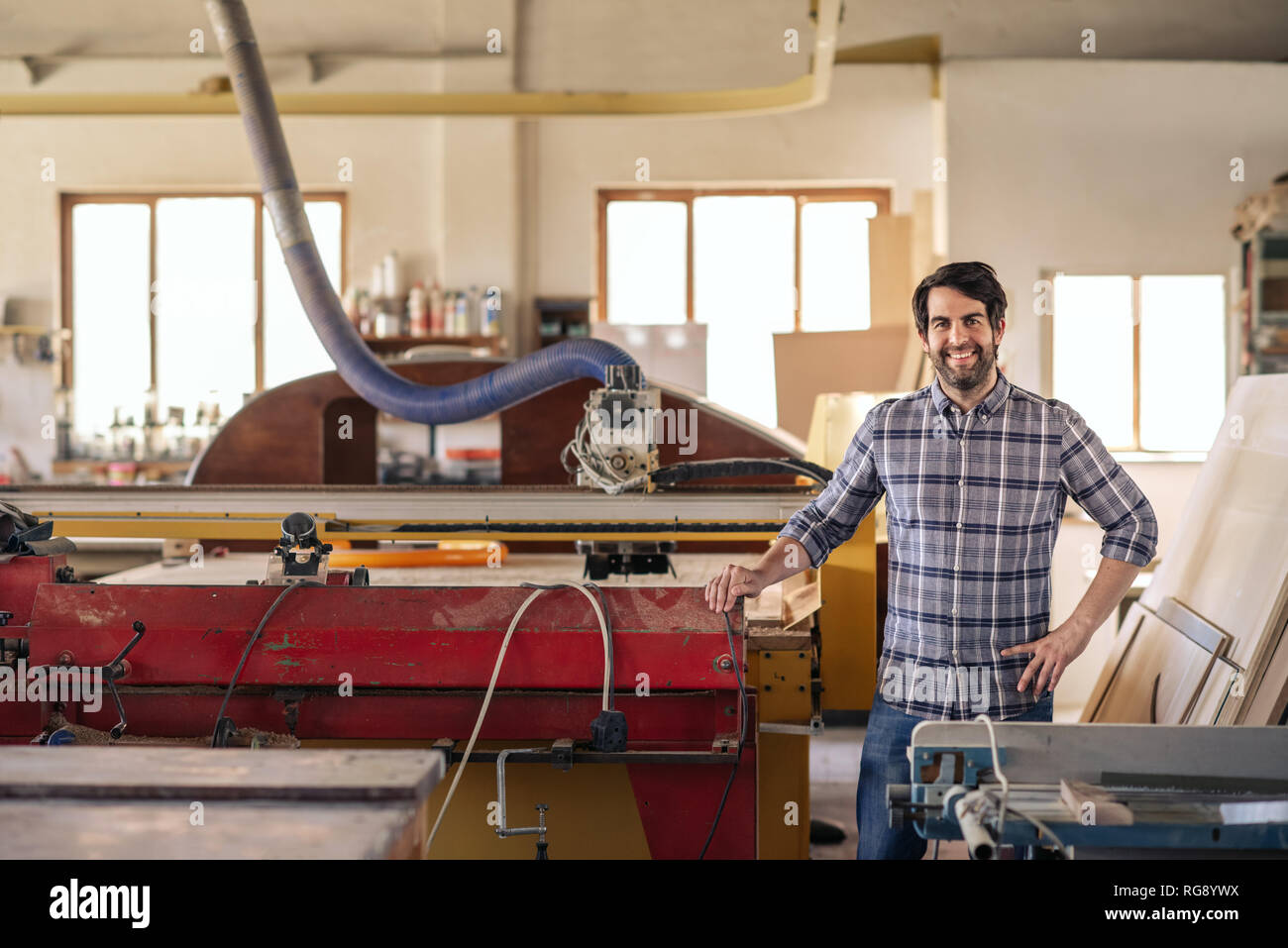 Smiling woodworker standing by equipment in his workshop - Stock Image