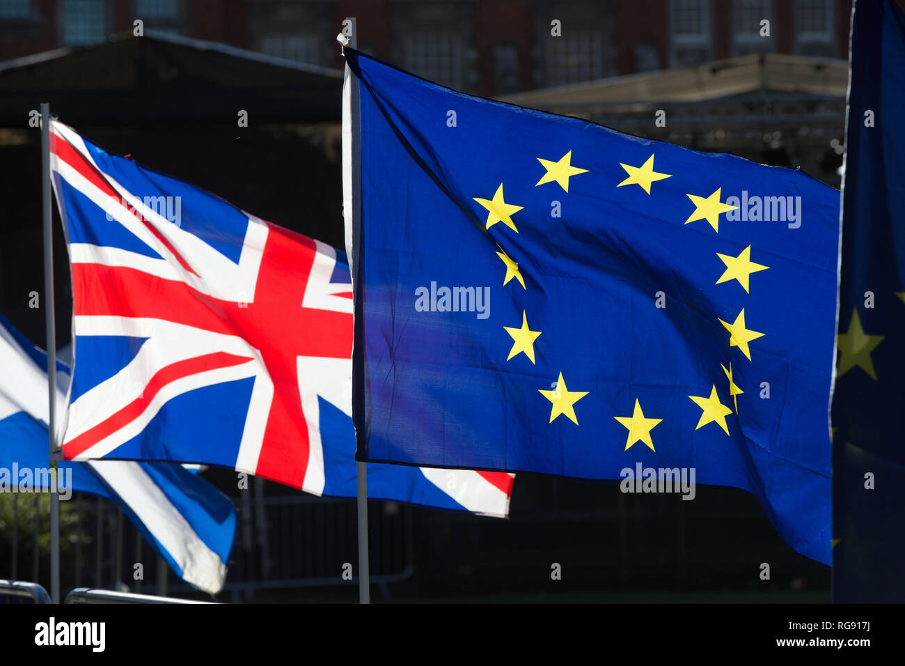 Anti-Brexit campaigners wave Union and European Union flags outside the Houses of Parliament, London. - Stock Image