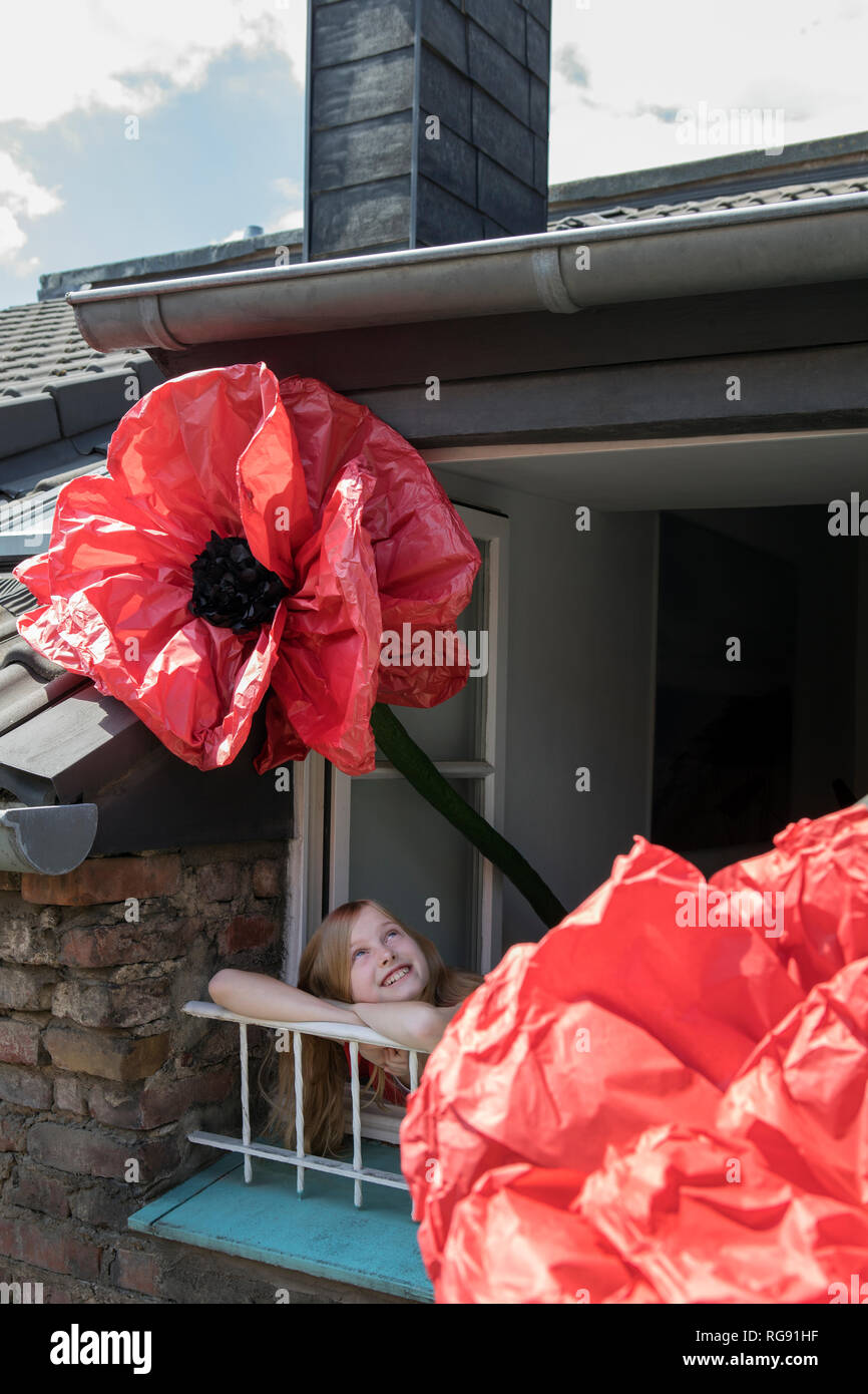 Happy girl with oversized redc artifical flower leaning out of window - Stock Image
