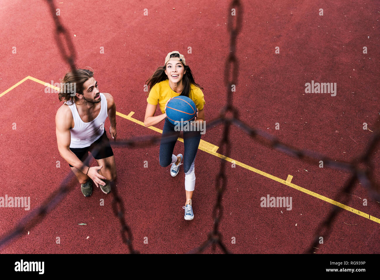 Young man and woman playing basketball on basketball ground Stock Photo