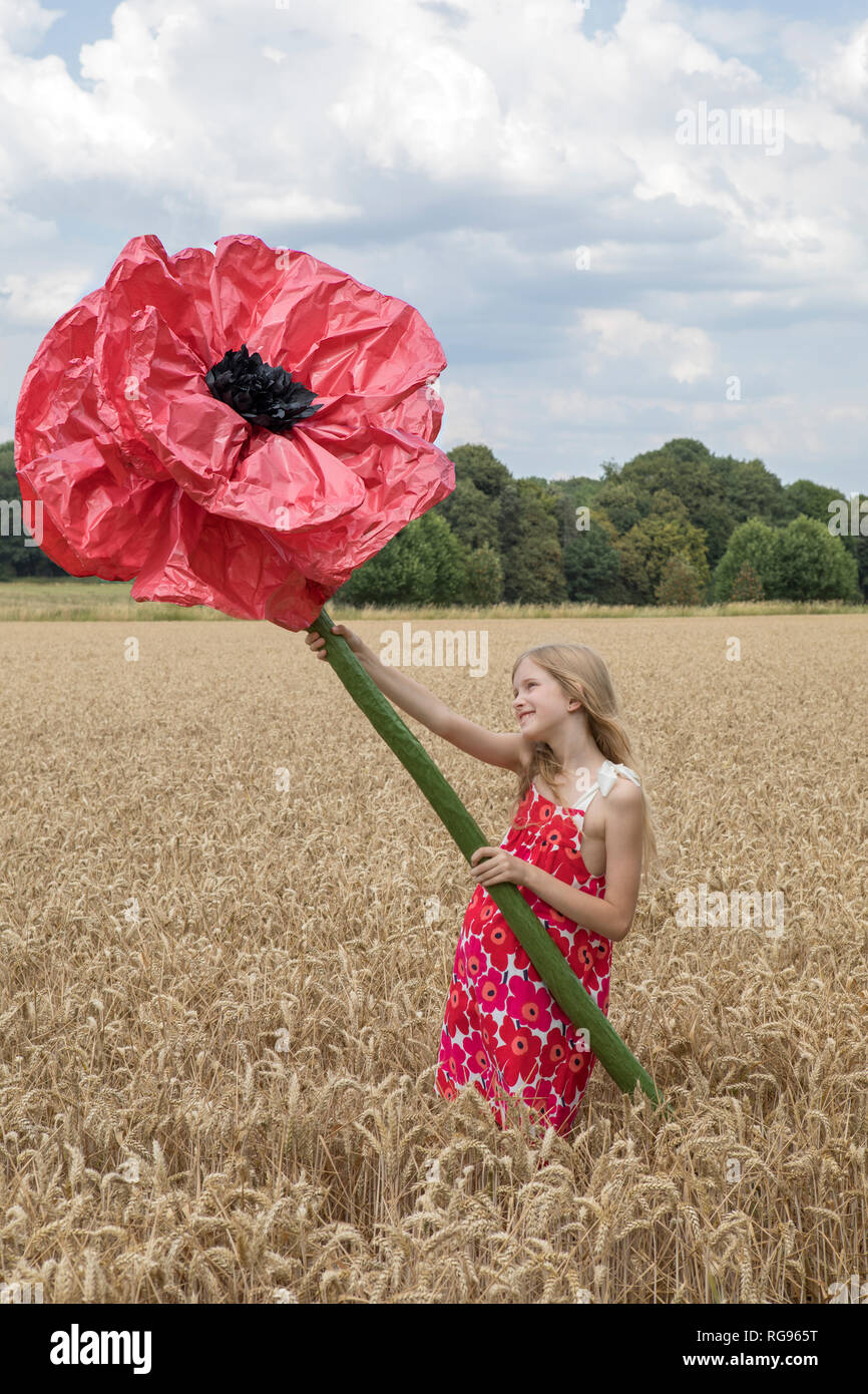 Smiling girl standing on a field with oversized red artificial flower - Stock Image