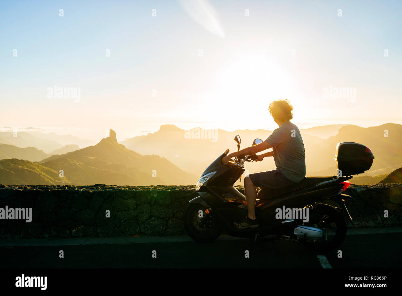 Spain, Canary Islands, Gran Canaria, man on motor scooter watching sunset over mountainscape - Stock Image