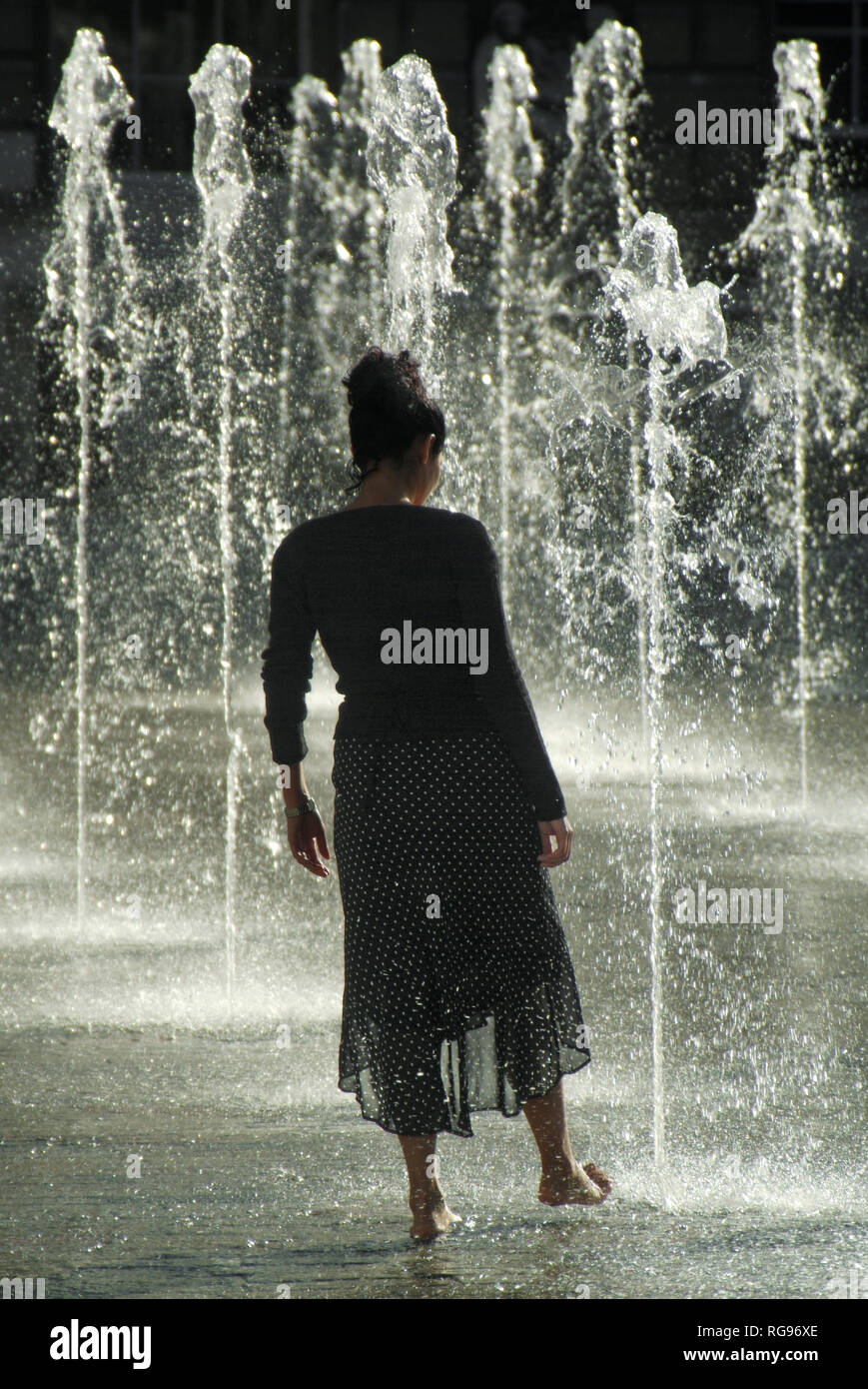 Concept testing & dipping toe in water of feature fountain silhouette back view tall young fun woman cooling off hot summer weather  London England UK - Stock Image