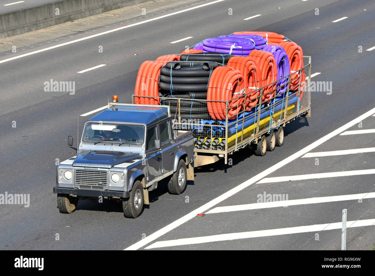 View looking down on Land Rover Defender & trailer transport of assorted colour coil & straight flexible plastic pipe tubing driving along UK motorway - Stock Image