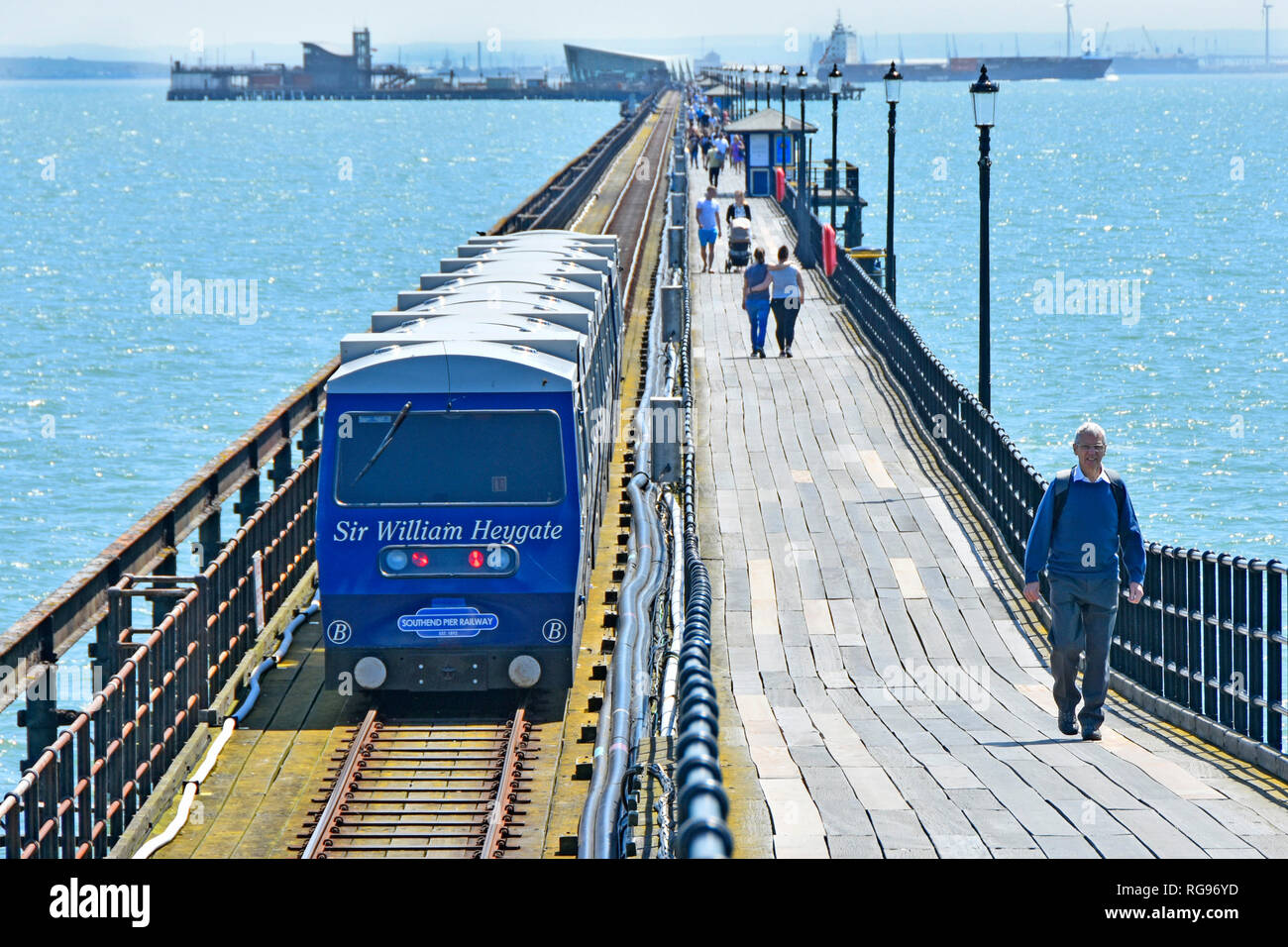 Two choices getting to distant 1.34 miles pier head in River Thames Estuary on Southend pier  walkers choice alongside public transport train Essex UK - Stock Image