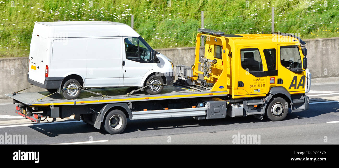 Looking down from above side view AA Renault breakdown truck tranporting white Ford Transit van secured by webbing restraints driving on UK motorway - Stock Image