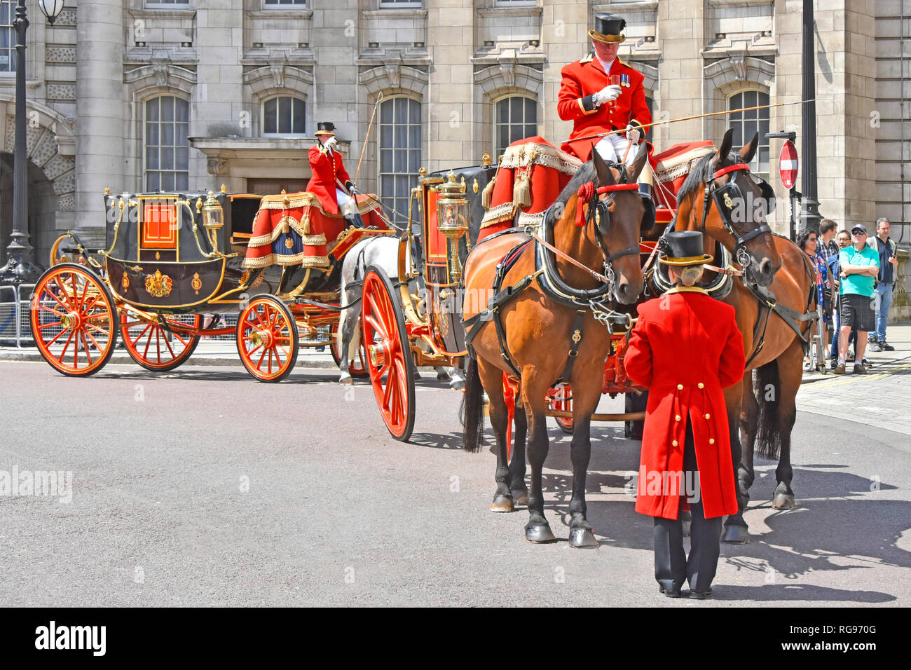 Two horse drawn State Landaus carriages wait at Admiralty Arch with coachman & footman taking refreshments on hot summers day London street scene UK - Stock Image