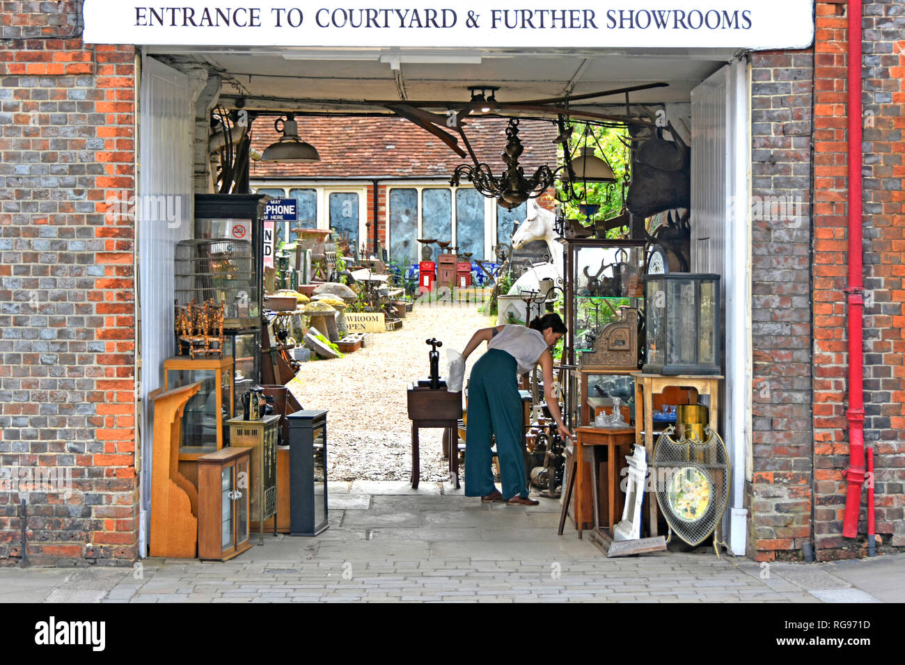 Woman arranging display of antiques  collectables & bric a brac in entrance to dealer courtyard & showroom shop at Hungerford Berkshire England UK - Stock Image