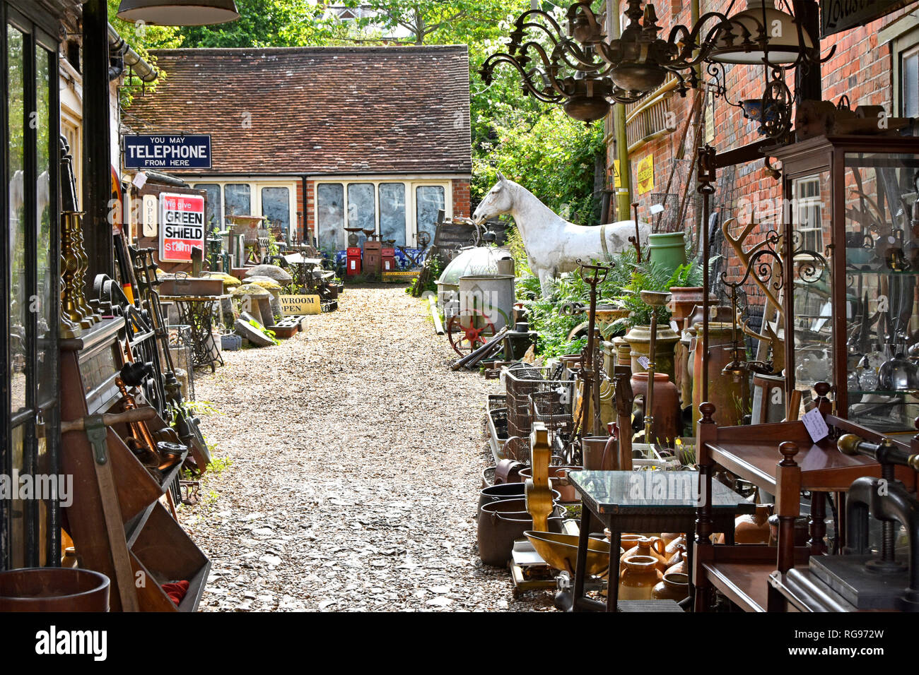 Display of historical antiques  collectables & bric a brac in dealer courtyard & showrooms with Green Shield sign at Hungerford Berkshire England UK - Stock Image