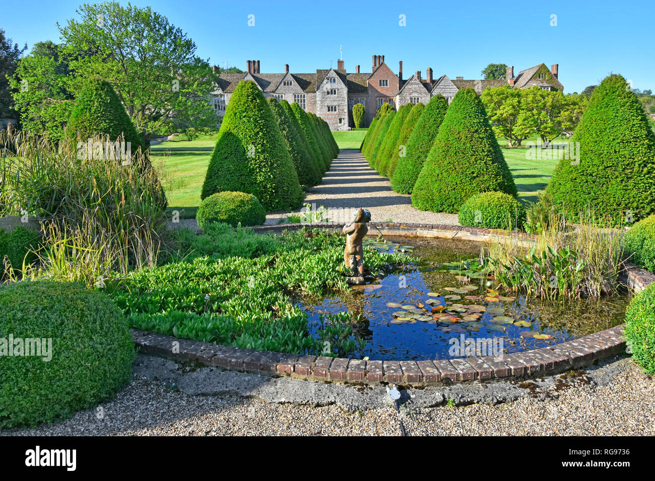 Elizabethan rural garden topiary & path with pond in historic parkland & gardens rows of repeat conifers Littlecote House beyond Wiltshire England UK Stock Photo