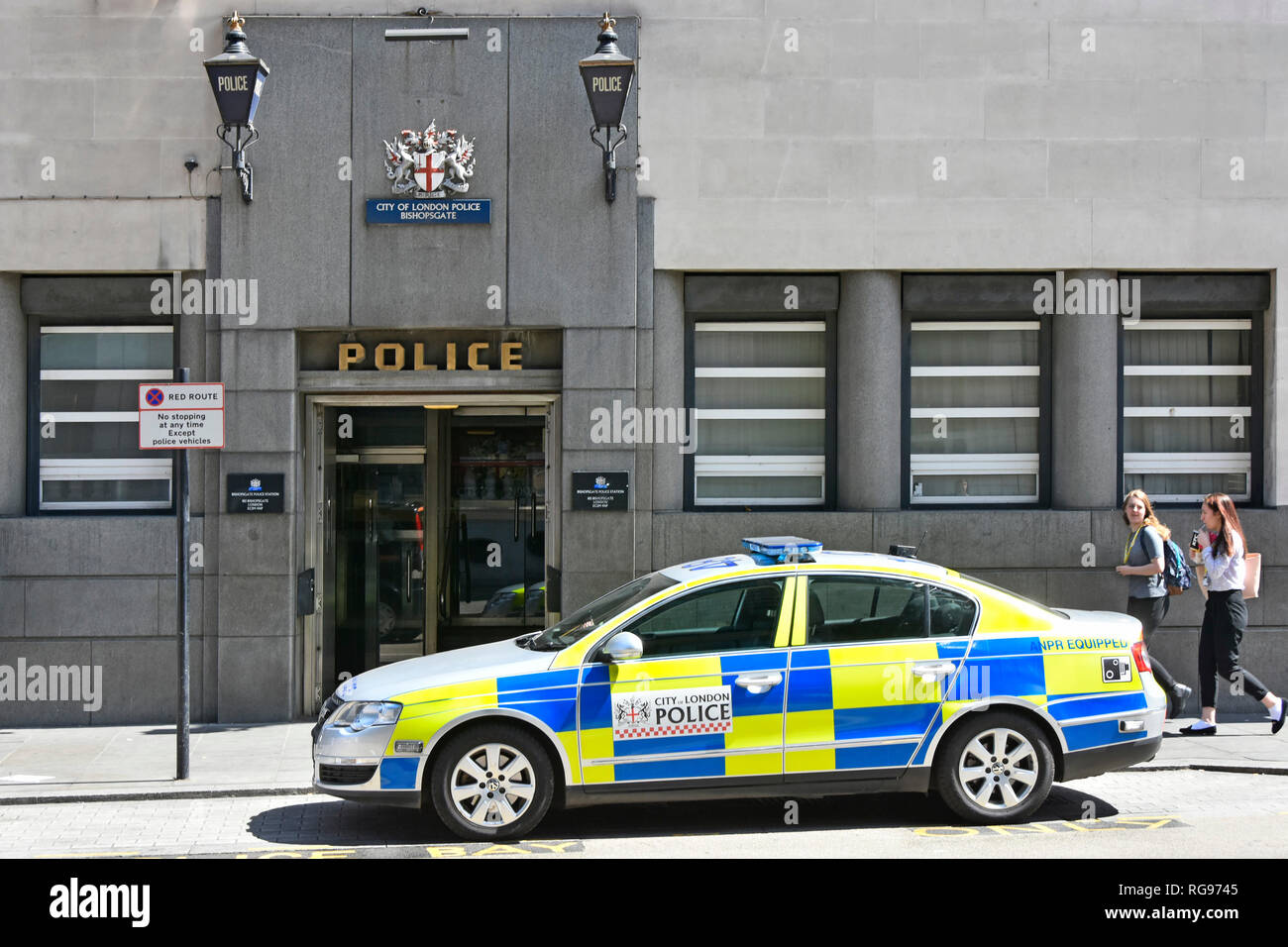 Street scene two blue lights above entrance on exterior of Bishopsgate City of London police station with police patrol car parked outside England UK - Stock Image