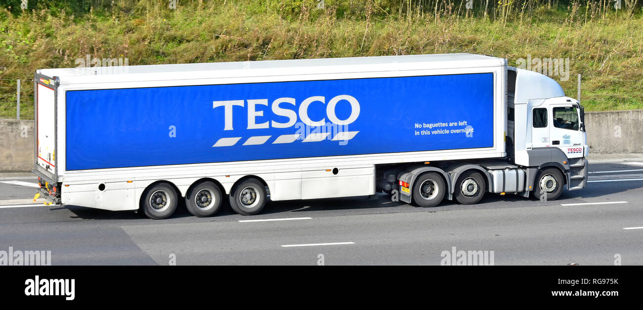 Side view of a Tesco supermarket hgv food supply chain juggernaut lorry truck & articulated trailer advertising business brand name logo UK motorway - Stock Image