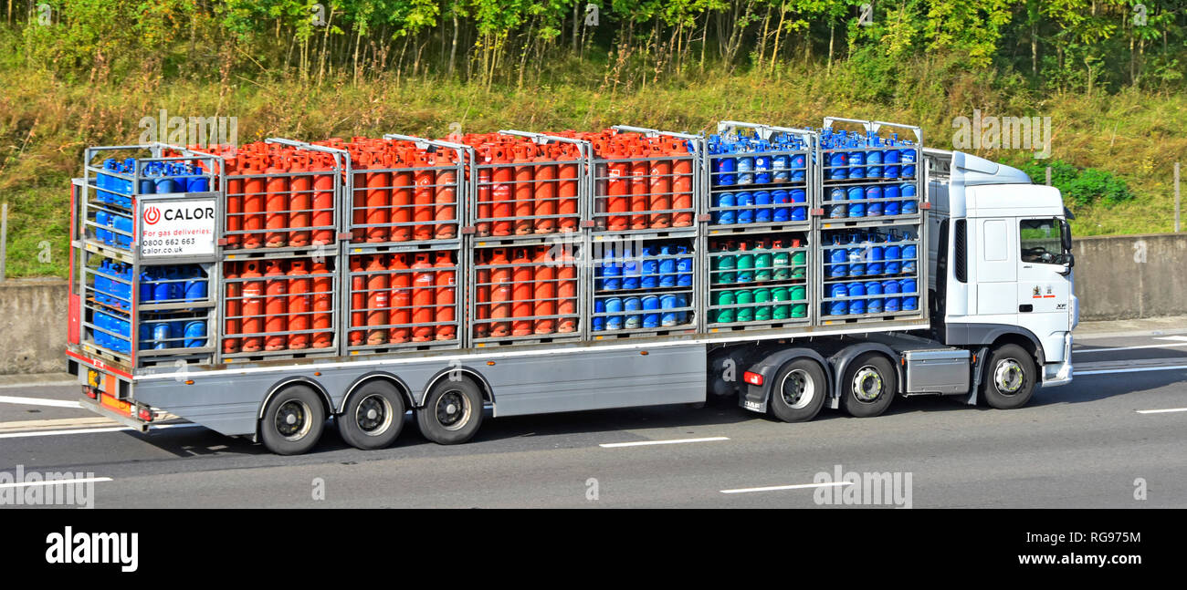 Side view of a Calor Gas brand supply chain juggernaut lorry truck & articulated trailer loaded with bottle butane & propane cylinders on UK motorway - Stock Image