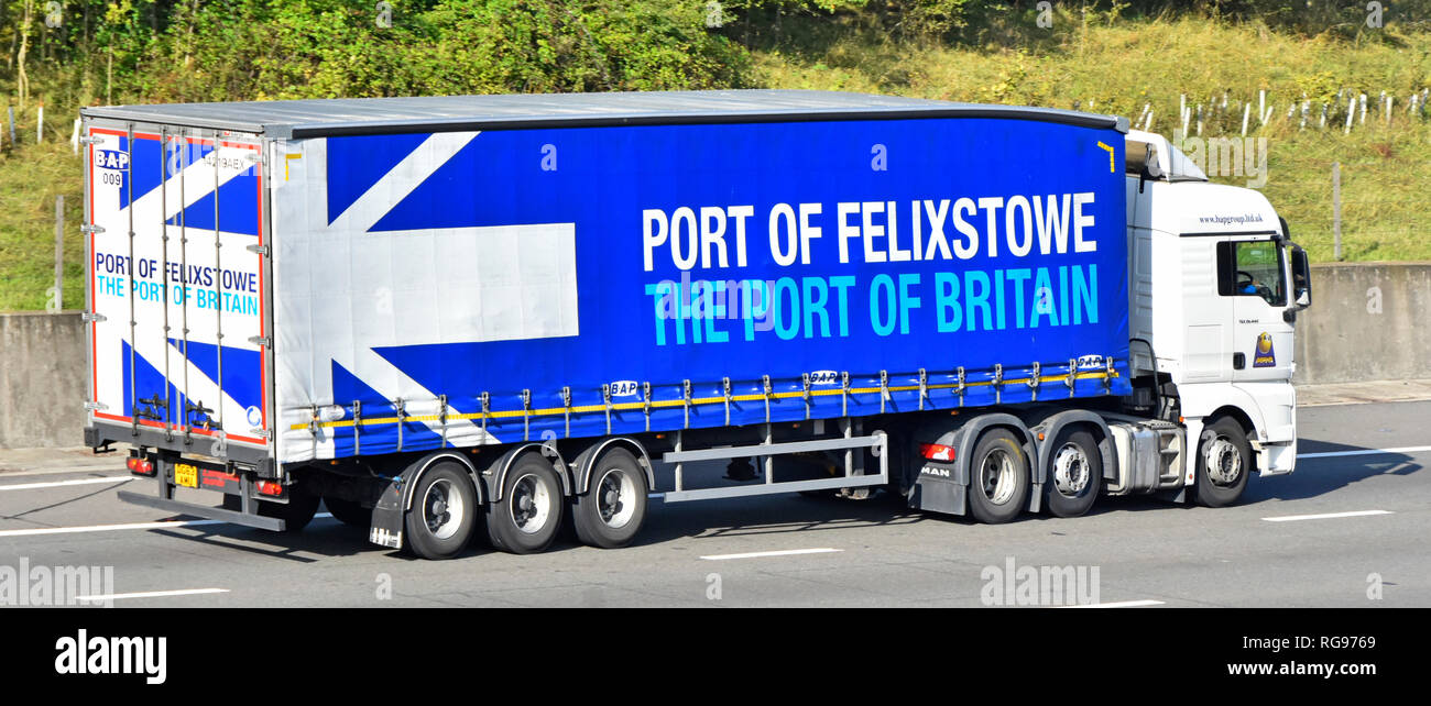 Side & back of white Man hgv lorry truck & trailer advertising & promoting Port of Felixstowe & Port of Britain on side of semi trailer uk motorway - Stock Image