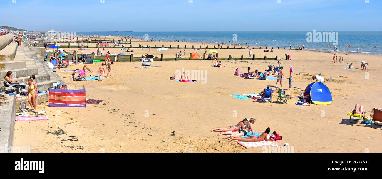 2018 hot weather summer crowds of holiday people on Essex seaside coast  family sand beach for safe play & sunbathing Frinton on Sea resort England UK - Stock Image