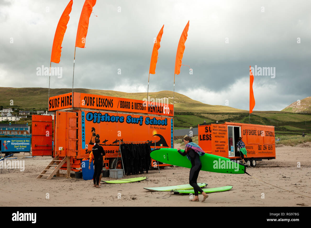 Orange surf board boards hire rentals beach shop shack cabin, wet suits hang on rail. Approved surf surfing school Ireland. Inch Beach surf rentals. - Stock Image