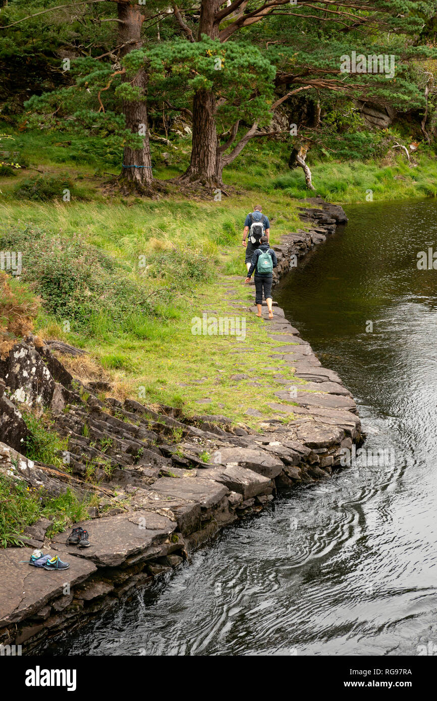 Hiking Ireland. Two backpackers couple tourists travellers walking barefoot along mountain river stream. Killarney National Park, Co. Kerry, Ireland. - Stock Image