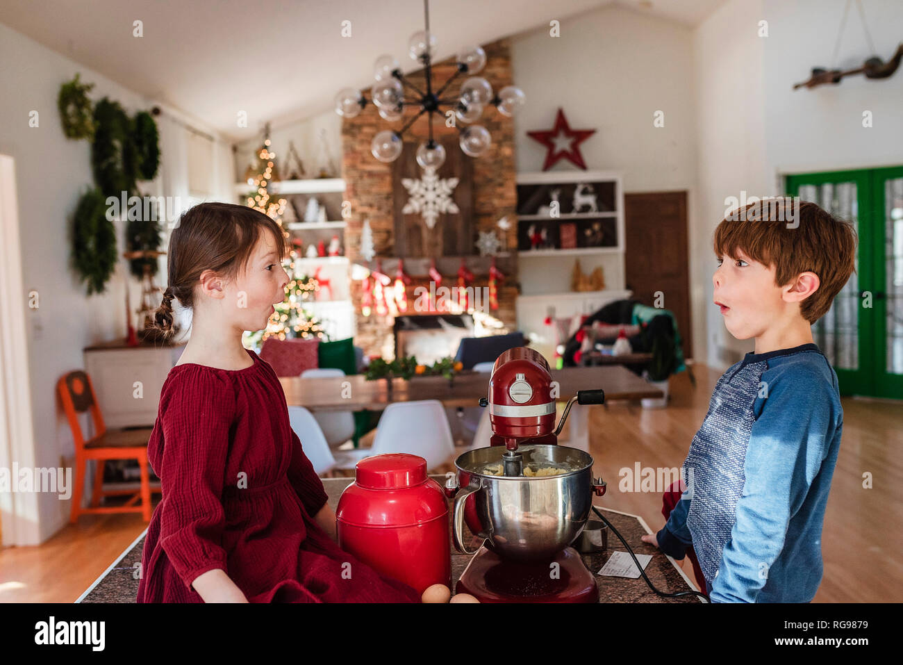 Two children messing about in the kitchen making a cake - Stock Image