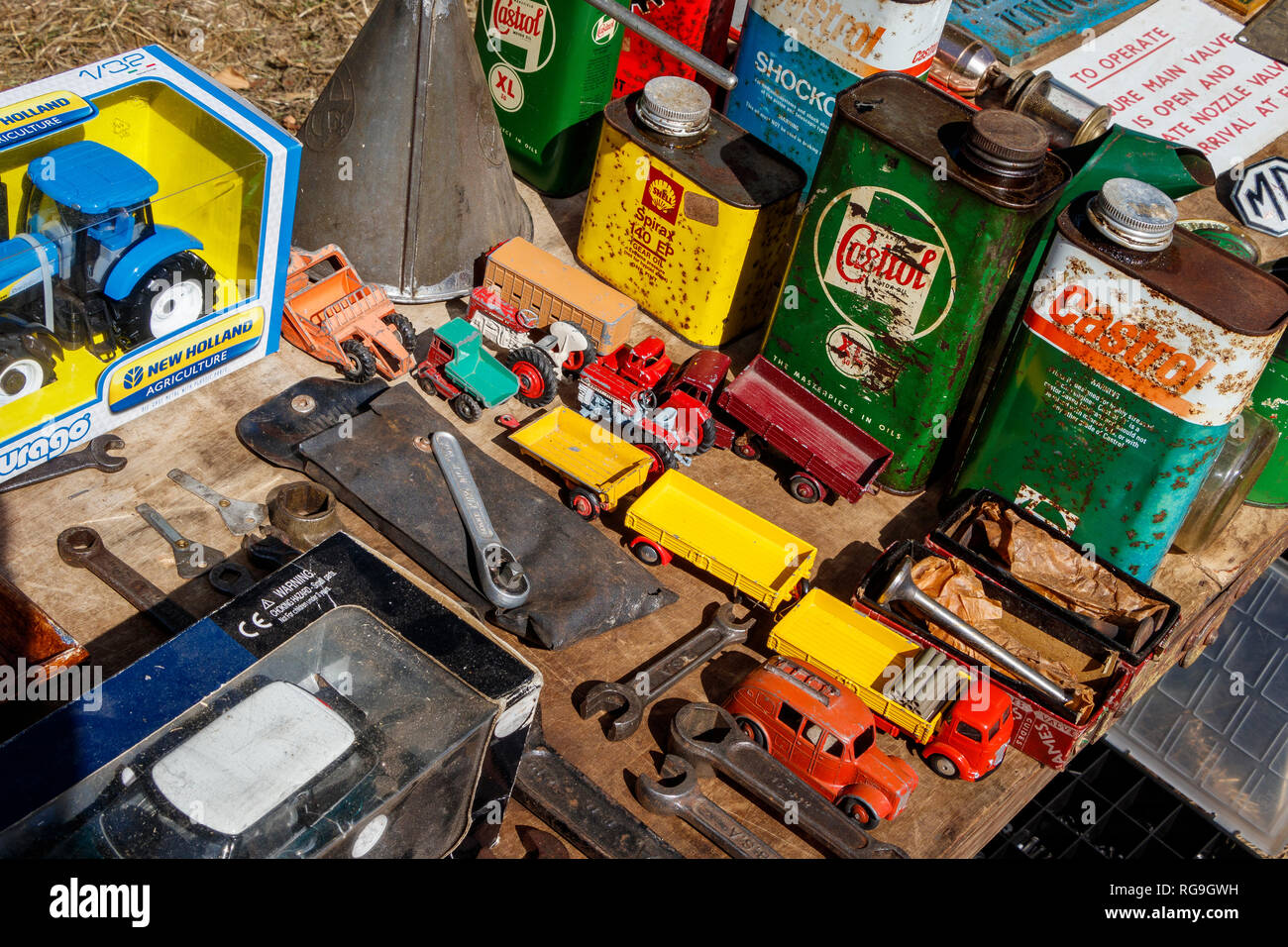Table of secondhand transport toys, oil cans, and tools. Stock Photo