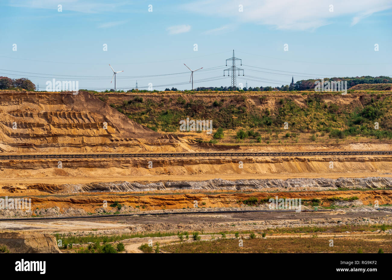 View to the edge of a lignite mining area with conveyor belts, wind power wheels in background, Etzweiler, Rhenish lignite mining area Stock Photo