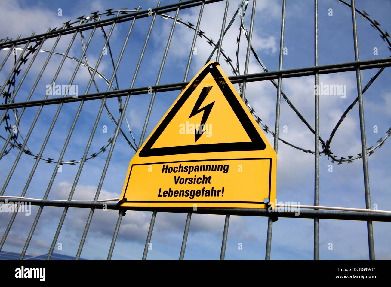 Signpost  and fence at an open space solar photovoltaic plant, Germany, Europe - Stock Image