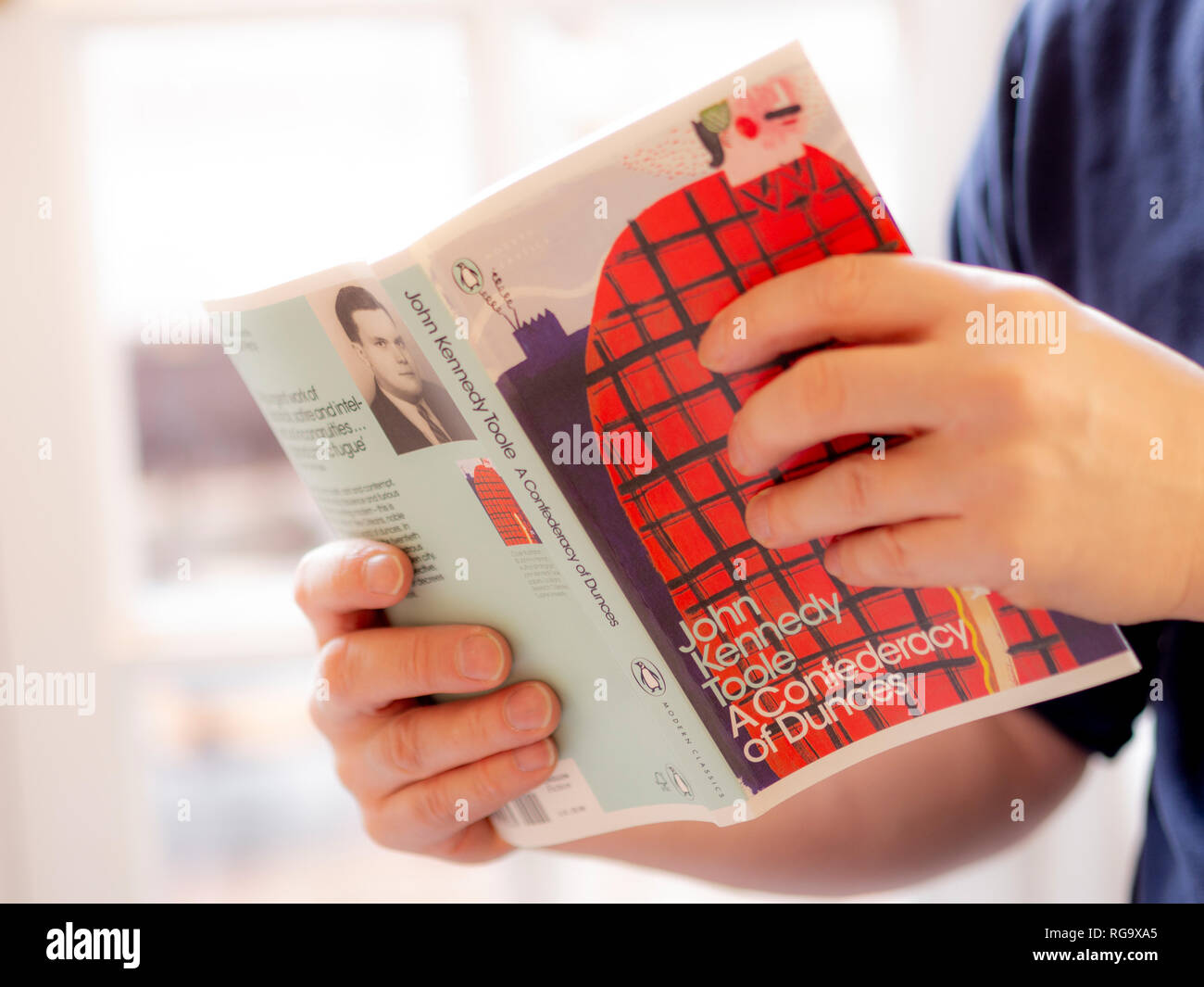 Male hands holding Book: A Confederacy of Dunces by John Kennedy Toole. Published by Penguin Modern Classics. - Stock Image