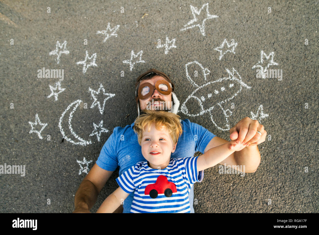 Portrait of mature man wearing pilot hat and his little son lying on asphalt painted with airplane, moon and stars - Stock Image