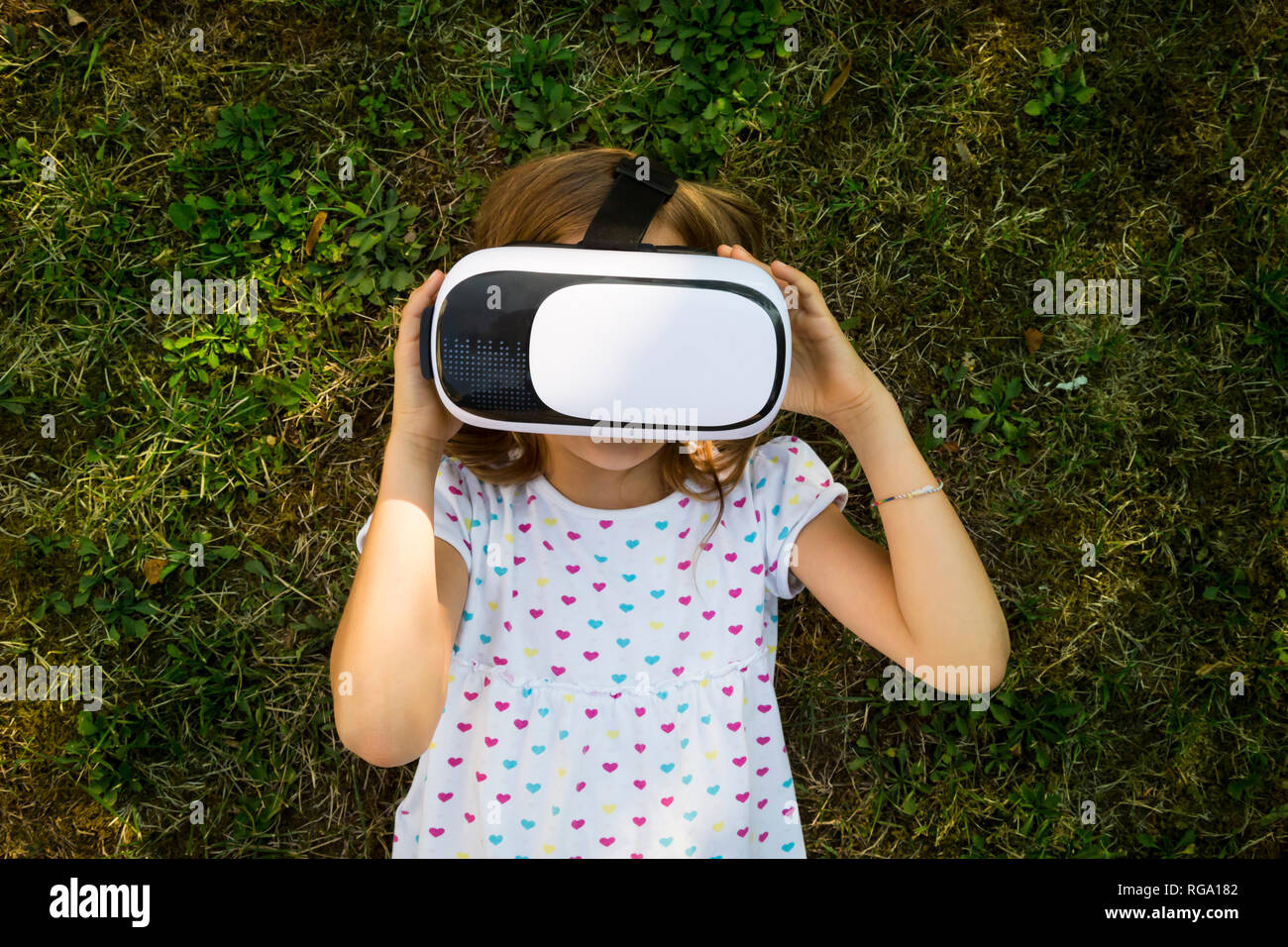 Little girl wearing Virtual Reality Glasses lying on meadow in the garden - Stock Image