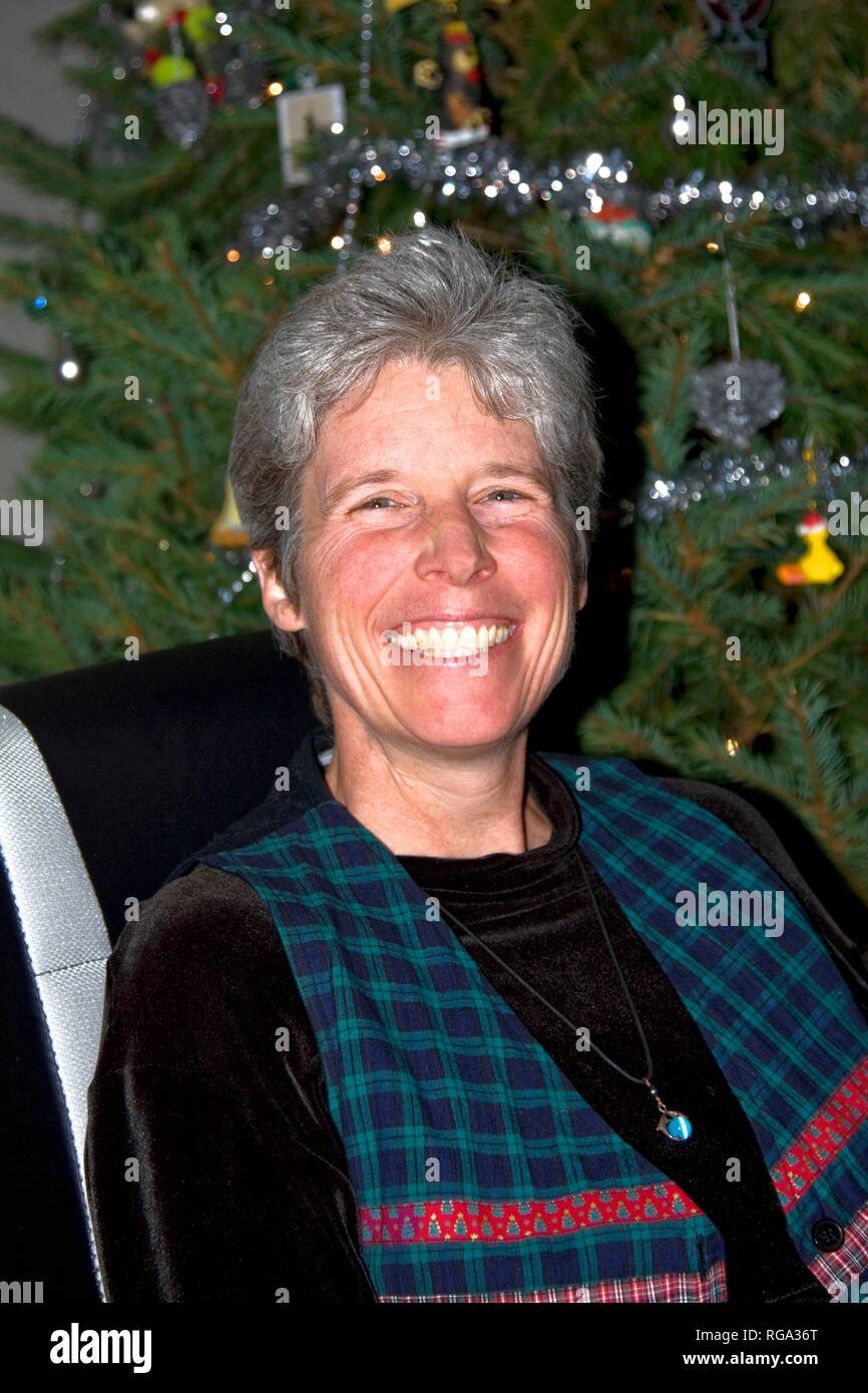 woman; portrait; wide smile; greying hair; Christmas tree; happy; attractive, vertical; MR - Stock Image