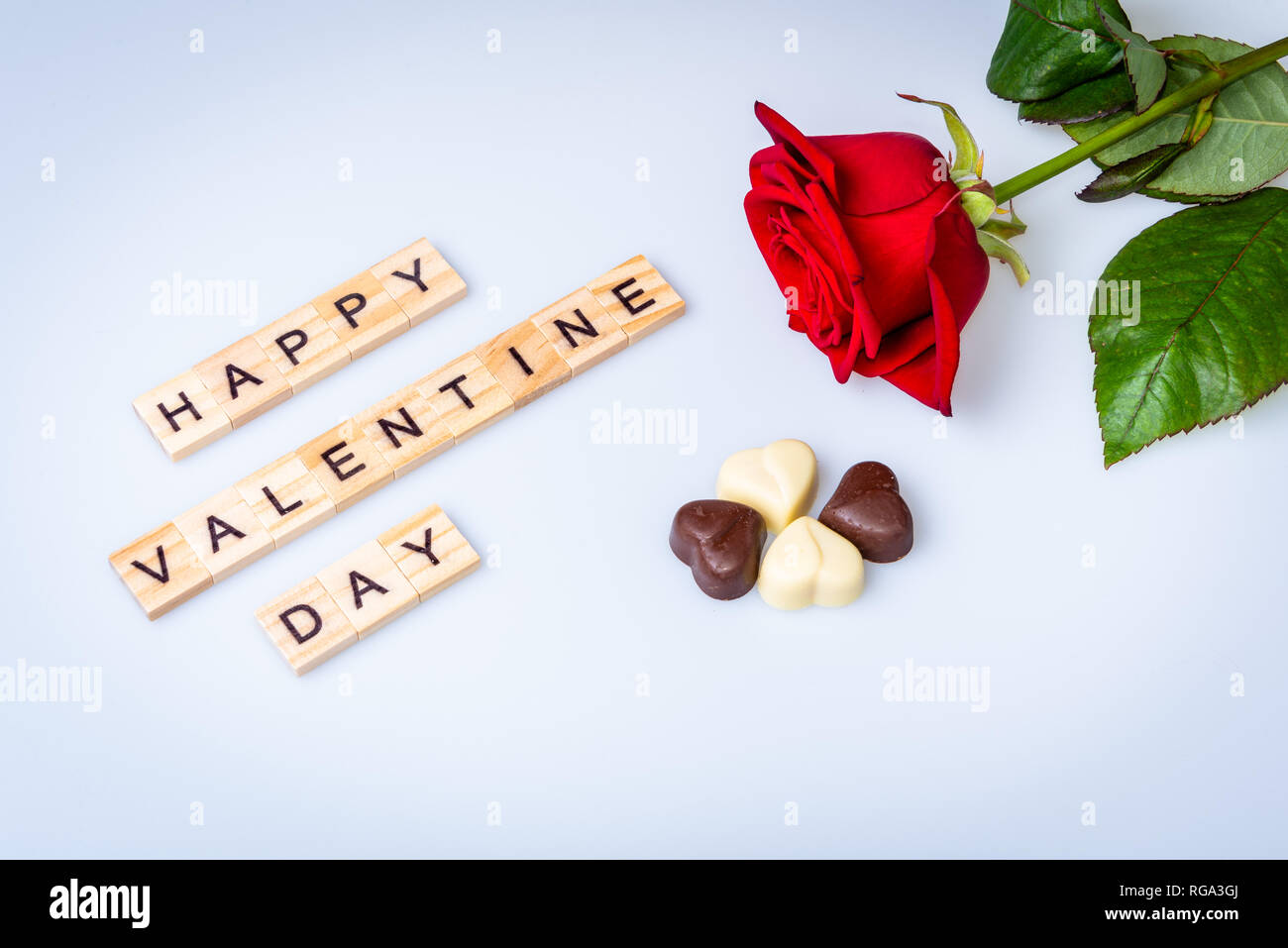 Happy Valentine day with red rose on white background with four chocolate hearts - Stock Image