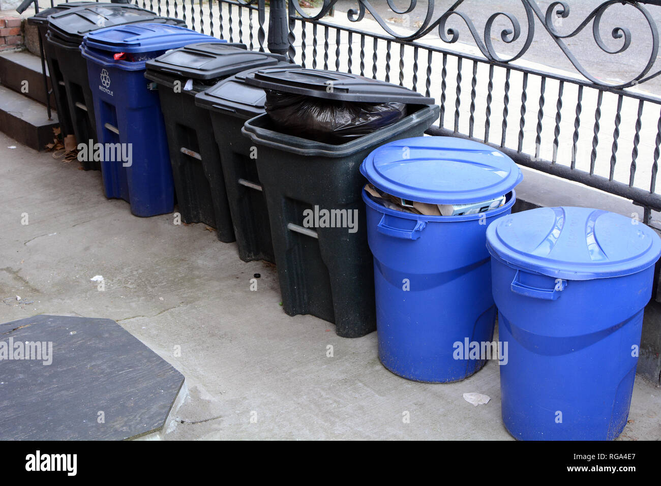 Trash and Recycling Bins In Front of Building at Sidewalk - Stock Image