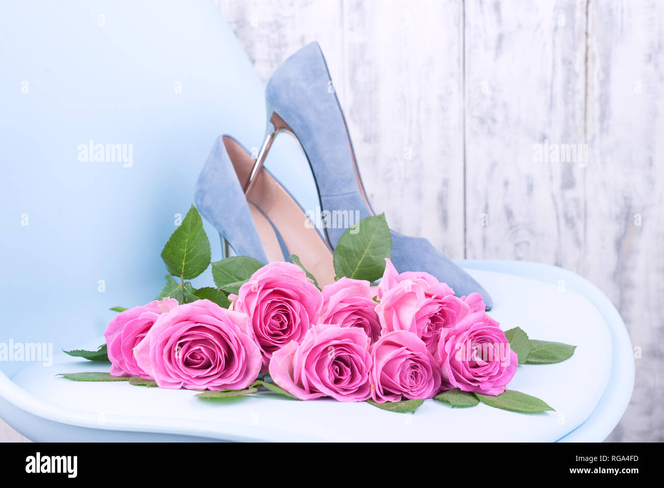 A Large Bouquet Of Pink Roses On A Blue Chair In Womens Shoes With