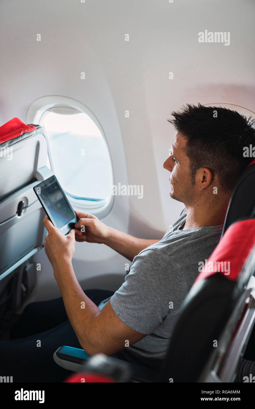 Man using ebook in airplane Stock Photo